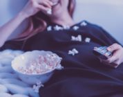 A woman eating pop corn and watching a free movie in her bed
